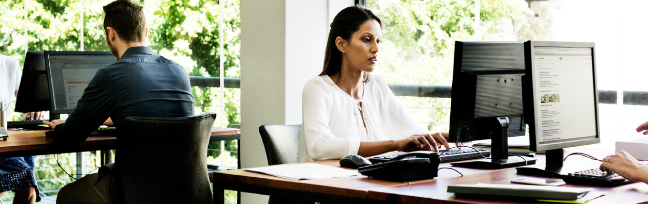 A woman sitting at desktop computer in office