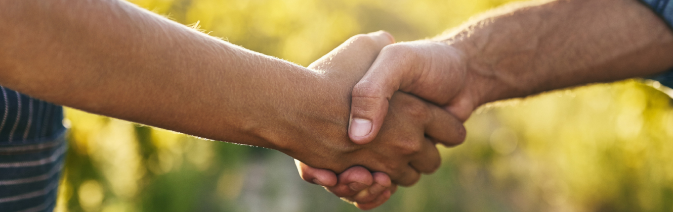 Two people shaking hands outdoors